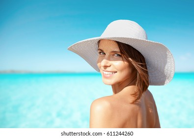 summer holidays, vacation, travel and people concept - smiling young woman in sun hat on beach over sea and blue sky background