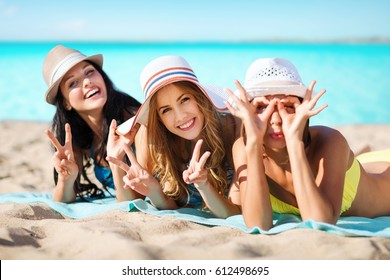 summer holidays, vacation, travel and people concept - group of smiling young women in hats lying over exotic tropical beach with background