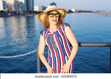 summer holidays, vacation, travel and people concept - smiling laughing young woman wearing sunglasses and hat on beach over sea background