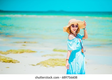 summer holidays, vacation, travel and people concept - smiling young woman in sun hat on beach over sea and blue sky background.copy space