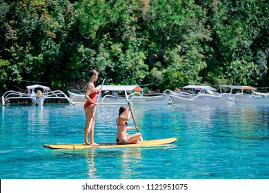 Summer holidays vacation travel. SUP Stand up paddle board. Young women sailing together on beautiful calm lagoon.