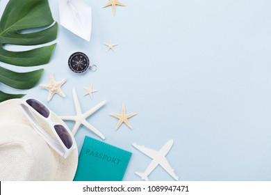 Summer holidays, vacation, travel and tourism background. Sunglasses, hat, passport, airplane, ship and tropic leaf on blue table top view. Flat lay.