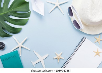 Summer holidays, vacation, travel and tourism background from sunglasses, hat, passport, notepad, palm leaf, airplane and ship. Top view. Flat lay.