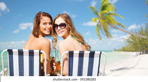 summer holidays, vacation, travel and tourism people concept - smiling young women with drinks sunbathing over exotic tropical beach with palm trees and sea shore background