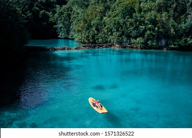 Summer holidays vacation travel. Young woman sailing on paddle board in beautiful calm lagoon.