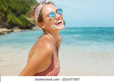 Summer holidays, vacations and resort concept. Beautiful glad young female wears swimsuit and trendy sunglasses, poses against sea background on beach, enjoys good rest in hot tropical country