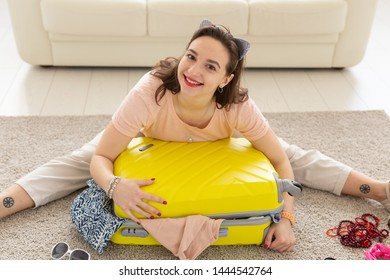 Summer holidays, voyage and traveler concept - Young beautiful woman collects a suitcase on a summer travel