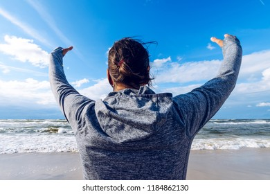 Summer holidays. Woman with her hands up on the sea wearing a sports hoodie