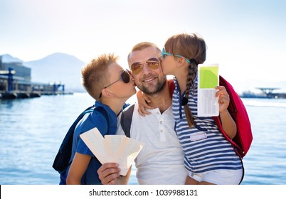 Summer holidays.Father with children are waiting summer sea vacation.