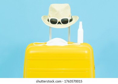 Summer holidays,vacation and travel concept.Yellow Suitcase or luggage bag,sun hat,glasses,medical face mask and alcohol Spray,the reopening of the  Tourism after the quarantine on blue background