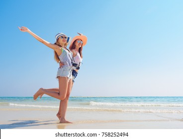 summer holiday,vacation,travel and people concept of smiling young women posting on beach over sea and blue sky background.Portrait of three young female friends walking on the sea shore looking