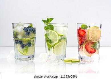 Summer homemade fruit and berries lemonade. Mojito, lemonade and sangria in tall glasses. Copy space