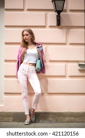 Summer hot sunny day. girl dressed in pink pants and white topic. girl stands near the wall like a model