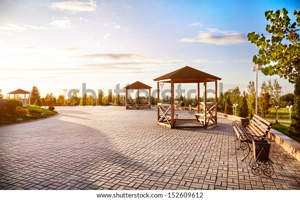Summer houses with benches at sunset sky background in dendra park of first president Nursultan Nazarbayev in Almaty, Kazakhstan
