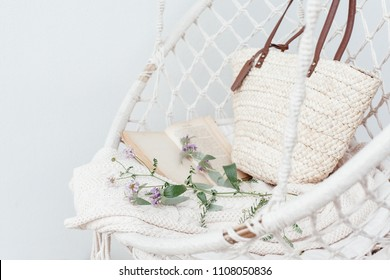 Summer hygge scene with hammock chair, book and flowers. Cozy place for weekend relax in the garden.