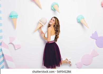 Summer, ice cream dream, attractive fashionable model in tulle skirt isolated on white background. Having fun, smiling to camera, expressing true positive emotions