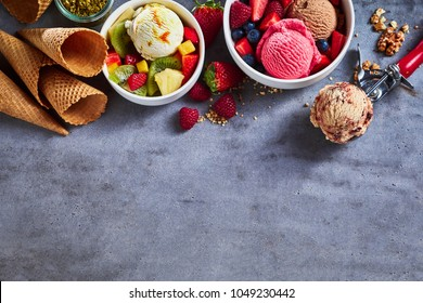 Summer ice cream flavors with fresh fruit salad, assorted berries, nuts, sugar cones and a scoop as a border on textured slate with copy space