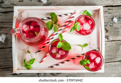 Summer iced drink - tea or juice with ice and mint. On rustic wooden table, with white tray, copy space, top view