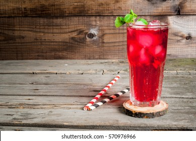 Summer iced drink - tea or juice with ice and mint. On rustic wooden table, copy space, horizontal