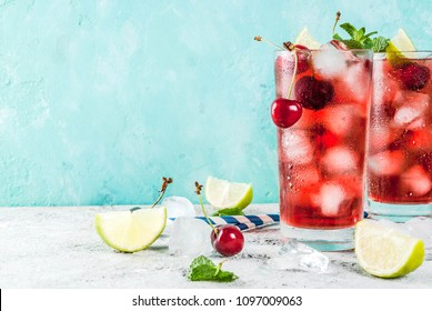Summer iced refreshment drink, cherry cola lemonade or mojito cocktail in tall glass, on light blue and grey background copy space