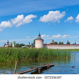 Summer idyllic landscape in the North-West of Russia View of the Kirillo-Belozersky monastery on the side of the lake duck with ducklings on the shore on wooden bridges.