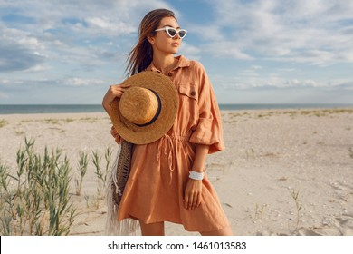 Summer image of beautiful  brunette  female in trendy  linen dress  jumping and fooling around  , holding straw bag. Pretty slim girl enjoying weekends near ocean.