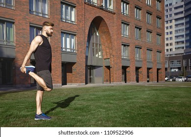 Summer image of male hipster with thick beard and stylish hairdo doing static quadricep stretch outdoors during running workout, standing on green grass with red brick building in background