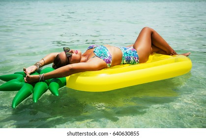 Summer image of pretty girl relaxing on an yellow inflatable pineapple mattress in the ocean. Wearing stylish high waist bikini and sunglasses. Smiling and enjoying life. Hands behind head. Sunbathing