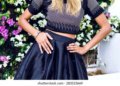 Summer image of pretty woman wearing stylish summer black clothes, trendy jewelry, posing in front of flowers, bright sunny colors.