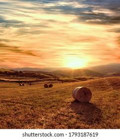 Sommerbild von Sizilien bei Sonnenuntergang auf einem Tal mit Heuballen auf Weizenfeld