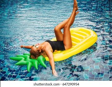 Summer image of stunning suntanned girl lying on yellow inflatable pineapple mattress in the pool. Feet up. Wearing stylish bikini and yellow mirrored sunglasses. Smiling and enjoying life. Sunbathing