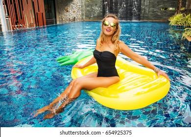 Summer image of stunning suntanned girl swimming on an yellow inflatable pineapple mattress in the pool. Wearing stylish black bikini and yellow mirrored sunglasses. Smiling, enjoying life. Sunbathing