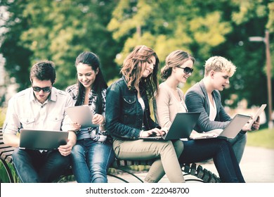 summer, internet, education, campus and teenage concept - group of students or teenagers with laptop and tablet computers hanging out