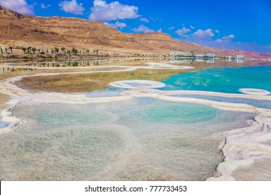 Summer, Israel. The evaporated salt has developed into fantastic patterns. Very salty water in the Dead Sea glows with turquoise light. The concept of ecological and medical tourism