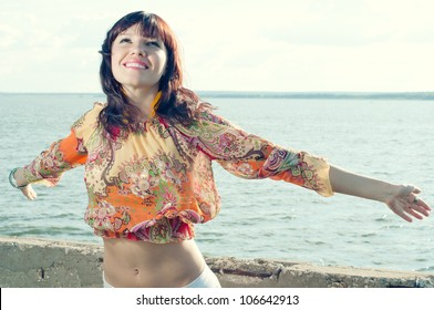 Summer joy: happy young woman standing on the shore with her arms outstretched