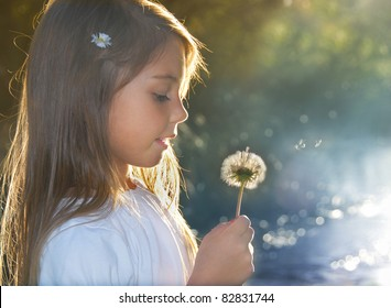 Summer joy, little girl blowing dandelion at sunset near the river