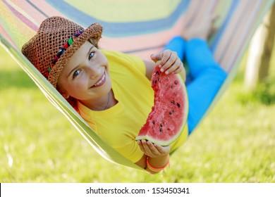 Summer joy - lovely girl eating fresh watermelon in colorful hammock