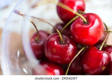 summer juicy berries - red cherries in a glass bowl, close up on a wooden table