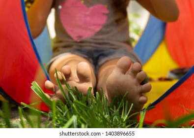 Summer kid background. Kids feet on green grass.