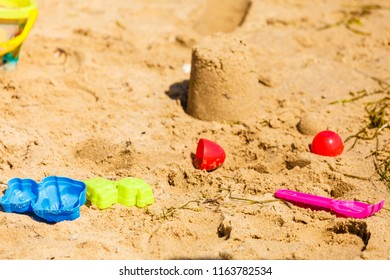 Summer kids toys on sandy beach druing summertime. Fun accessories objects concept.