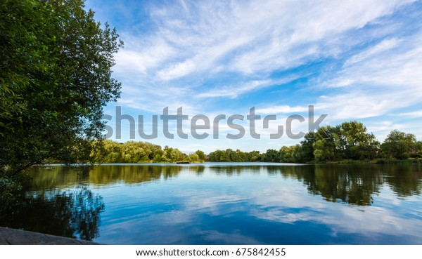 Summer lake landscape with green trees and bush, blue sky and calm water in Goldsworth Park, Woking, Surrey, England. Horizontal low wide angle perspective