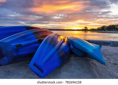Summer Lake Sunrise Background. Kayaks line the lakeshore with vibrant and beautiful sunrise colors in the background. Grand Traverse Bay in Traverse City, Michigan, USA.