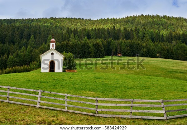 Summer landscape in Austria with fence, green meadows and a white Church