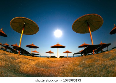 Summer landscape of beach resort with sand and straw umbrellas under sun light