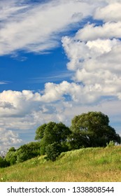 Summer landscape. Bright blue sky. Beautiful white clouds. River bank. Hills in bright green grass and meadow flowers. Sonechno. Warm. - Shutterstock ID 1338808544