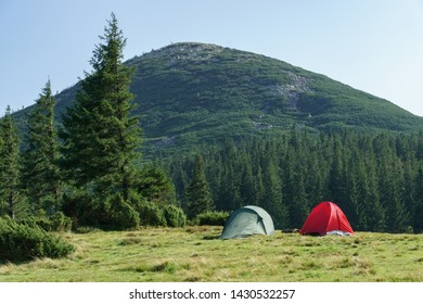 Summer landscape with camping tents on mountain valley and hills mountains peak.