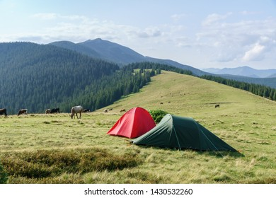 Summer landscape with camping tents on mountain valley and hills mountains.