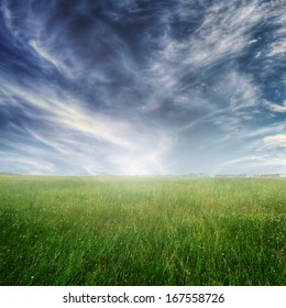 Summer landscape with green grass and blue dramatic sky