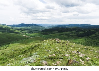 Summer landscape with green grass, country and mountains.