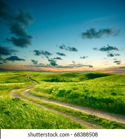 Summer landscape with green grass, road and dramatic sky